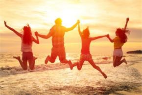 Springende mensen op een strand